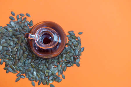 Organic pumpkin seed oil with pumpkin seeds on orange background. Image with copy space, top view