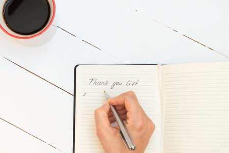 Directly above view of woman's hand writing in a gratitude journal thank you list with coffee mug, pen on white wooden table, copy space