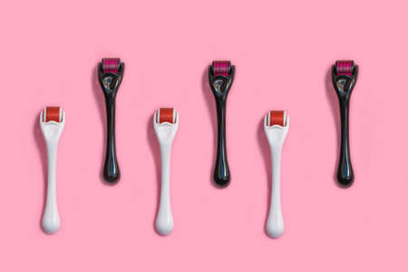 Micro needle derma roller for home face care on light pink background. Top view, flat lay, pattern