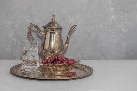 斋月禁食概念。在葡萄酒盘子的水和干燥日期在中立背景