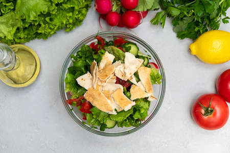 Top view of Fattoush salad in a bowl with ingredients on neutral background