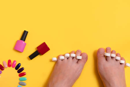 Top view of woman feet getting pedicure on yellow background. Nail care, pedicure, accessories