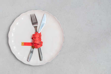 Fork and knife with red measuring tape on white plate. Diet and loose weight concept. Above view with place for text