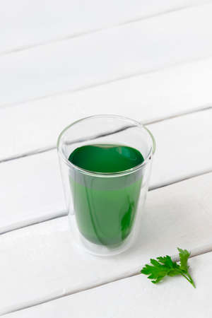 Water with liquid chlorophyll in a glass on white wooden table with copy space, vertical image