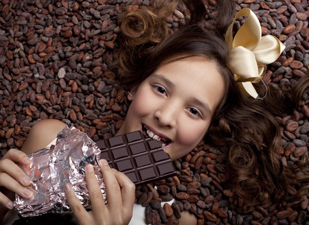 cacao: girl with chocolate on cocoa beans background Stock Photo