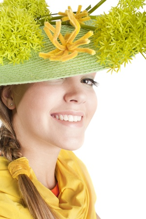 beautiful smiling girl with green hand made hat with greens and yellow flowers photo