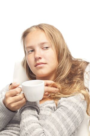 young beautiful caucasian girl with white cup are looking down, isolated on a white photo