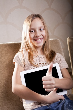 smiling positive caucasian school girl is with tablet computer at home photo