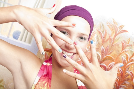 smiling beautiful caucasian girl  with hands which has colored nails photo