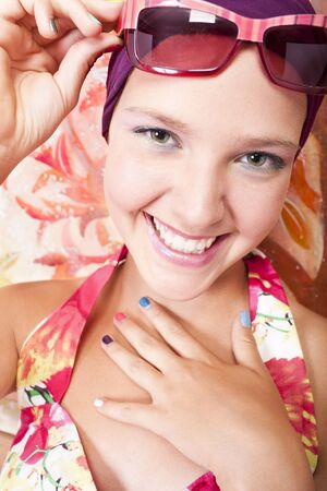 smiling beautiful caucasian girl closes her mouth with hands which has colored nails photo