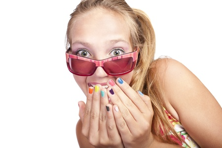 teenage girl dress: smiling beautiful caucasian girl closes her mouth with hands which has colored nails Stock Photo
