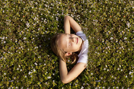 happy school girl is under the grass natural cover on the graund photo