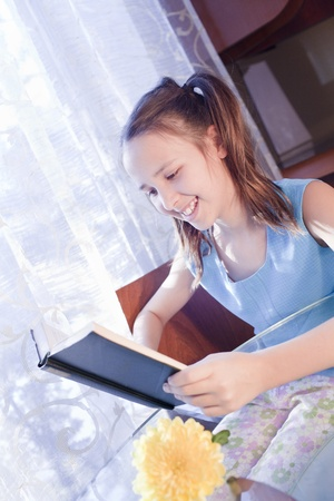 positive caucasian school girl with open book at home photo