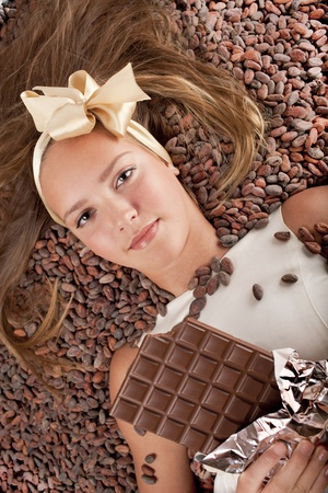 beautiful caucasian girl with chocolate is on a cocoa beans Stock Photo - 13138021