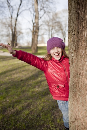 smiling schoold age girl is in the park in sun day photo