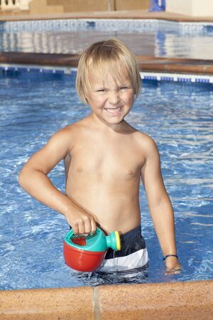 boy of 4 years old in the swimming pool are looking at the camera photo
