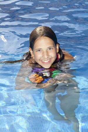 11 years: smiling 11 years old girl is in the swimming pool with ball