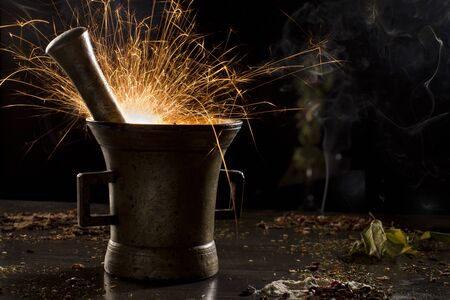 metal mortar with sparkling fire, surrounded with spices photo