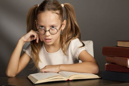 eight years old: eight years old girl with books looking up Stock Photo