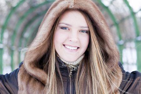 whitem: caucasian smiling girl in fur coat is in the park