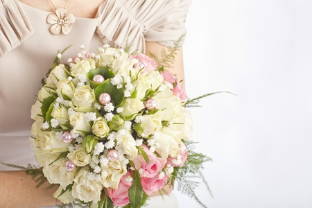 perls: bridal bouquet of white roses with perls on a pink dresses background