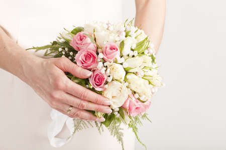 perls: bridal bouquet of white roses with perls on a pink dresses background with hands Stock Photo