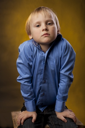 boy in a blue shirt and black trousers on the chair photo