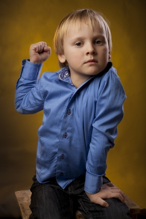 threatens: boy in a blue shirt and black trousers threatens a fist Stock Photo