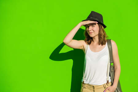 20 24: young beautiful girl in a hat on a background of green wall