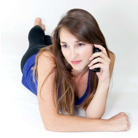 voicemail: young woman on the phone lying on white background Stock Photo