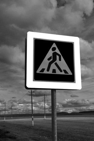 metal pole: A pedestrian crossing sign on sky background. Photo traffic sign on a metal pole. Stock Photo