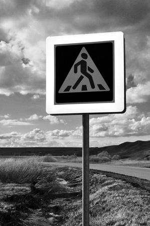 metal pole: A pedestrian crossing sign on old desert road. Photo traffic sign on a metal pole.