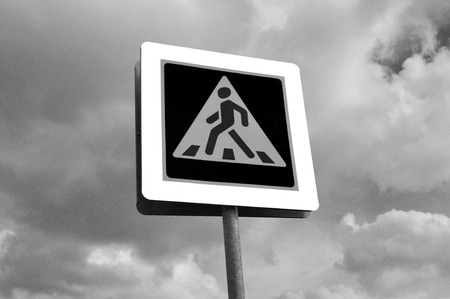 start to cross: A pedestrian crossing sign. Photo traffic sign on a metal pole.
