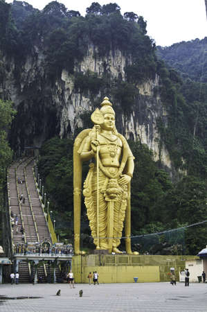 the large gold hindu statue in front of the batu caves in malaysia.