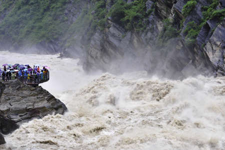 Tourists on a viewing platform looking out over the wild river at Tiger Leaping Gorge in Yunnan, China