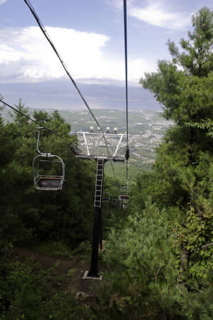 A chairlift going up a mountain pass in summer