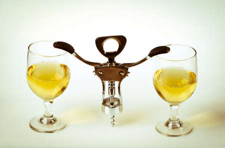 Glass of white wine and corkscrew isolated on a white background Stock Photo