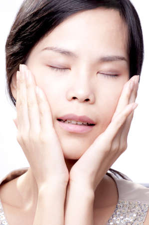 Young asian female with her hands on face in beauty shot