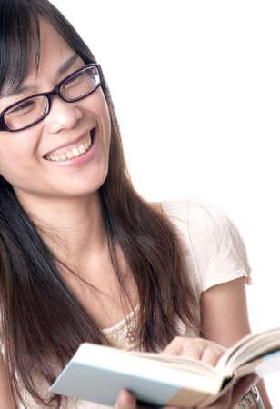 laughing out loud: Una mujer asi�tica joven leyendo un libro y ri�ndose a carcajadas con gafas Foto de archivo