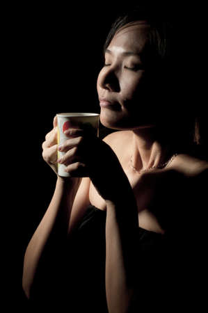 Attractive woman  with an aromatic coffee in hands isolated on black background