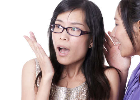 Girl telling a secret to another - gossip isolated over a white background Stock Photo