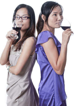 Two women next to each other in a bar having a drink