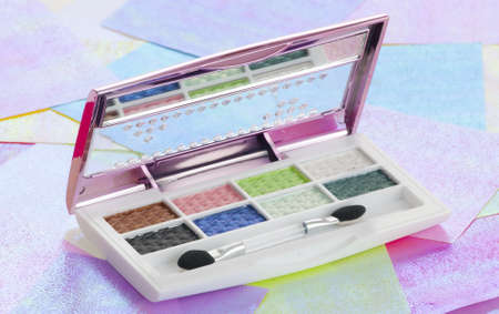Eye shadow kit over colourful papaers background photo