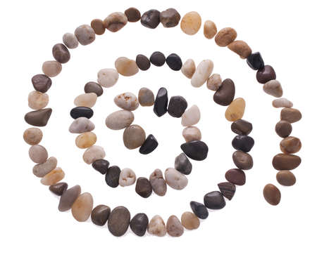 Stone spiral made from the beach pebbles isolated on the white