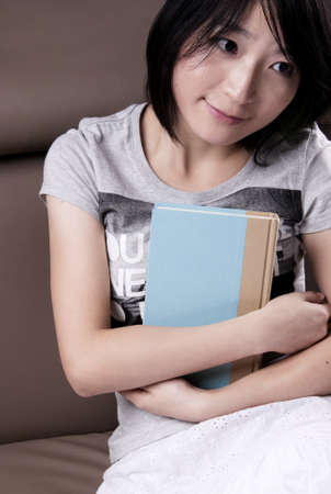 Thinking beautiful girl with the book sitting on sofa