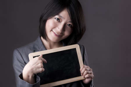 Happy woman in suit pointing to blackboard