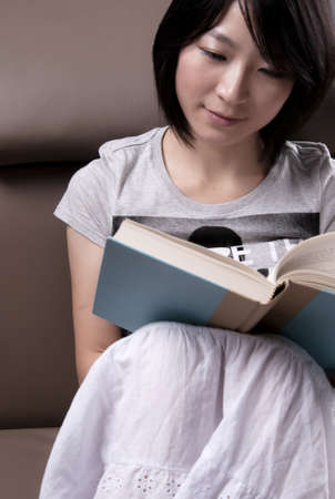 Portrait of a young woman sitting on sofa reading book