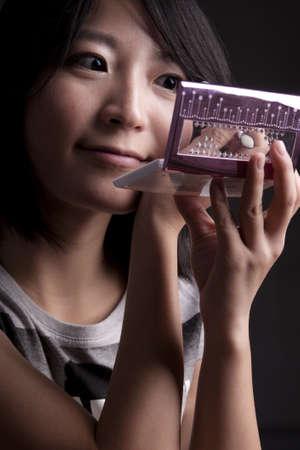 a young fashionable asian girl applying eye shadow and make-up