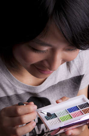A young fashionable asian girl applying eye shadow and make-up Stock Photo