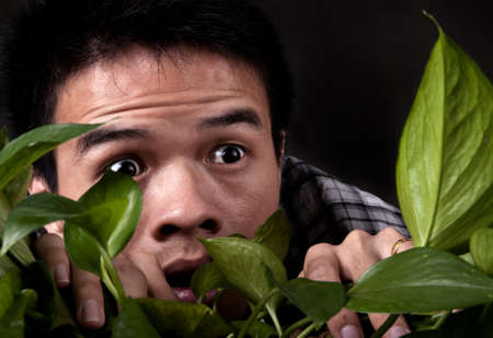An asian man is suprised and scared  as he looks through a jungle plant Stock Photo